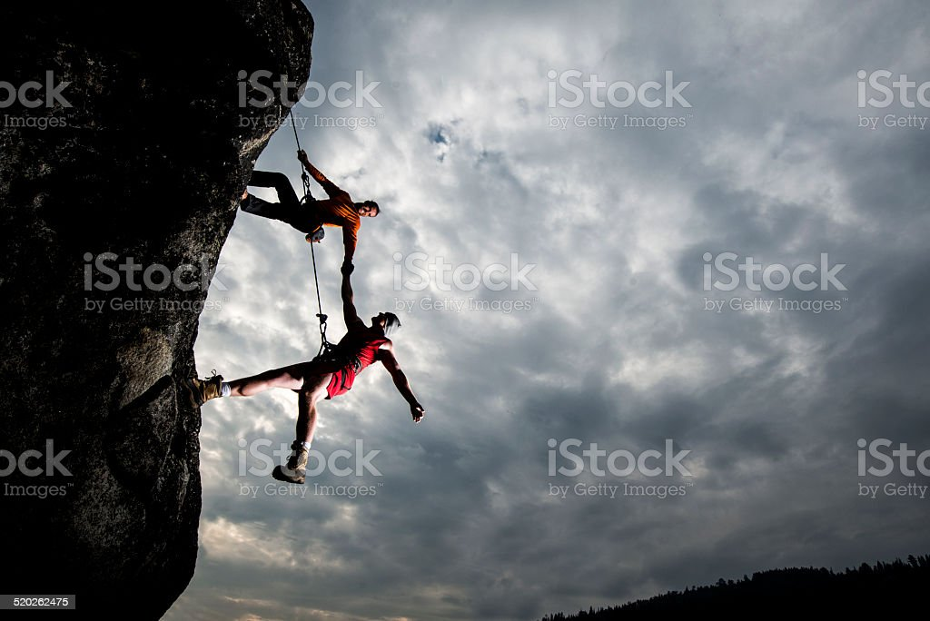 Rock climber assisting another stock photo
