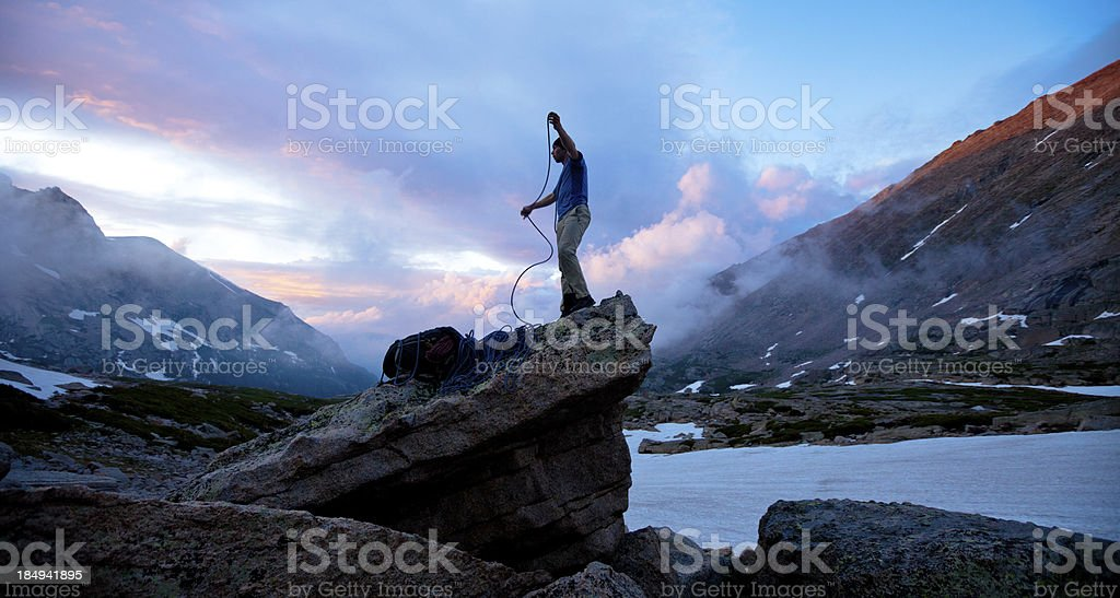 Rock climber at sunset coiling rope stock photo