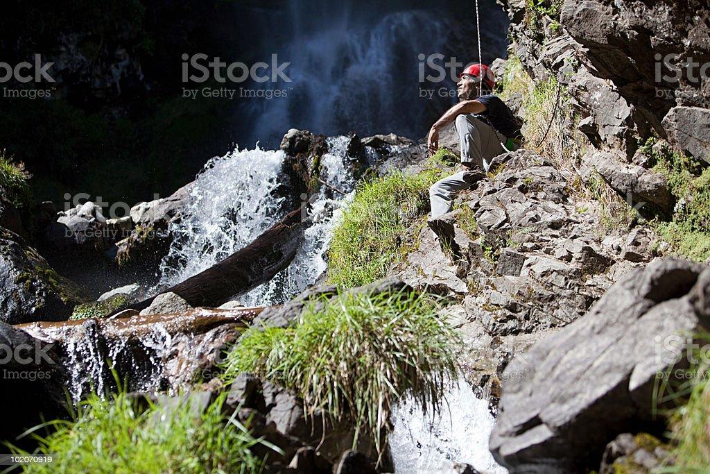 Rock climber by waterfall stock photo