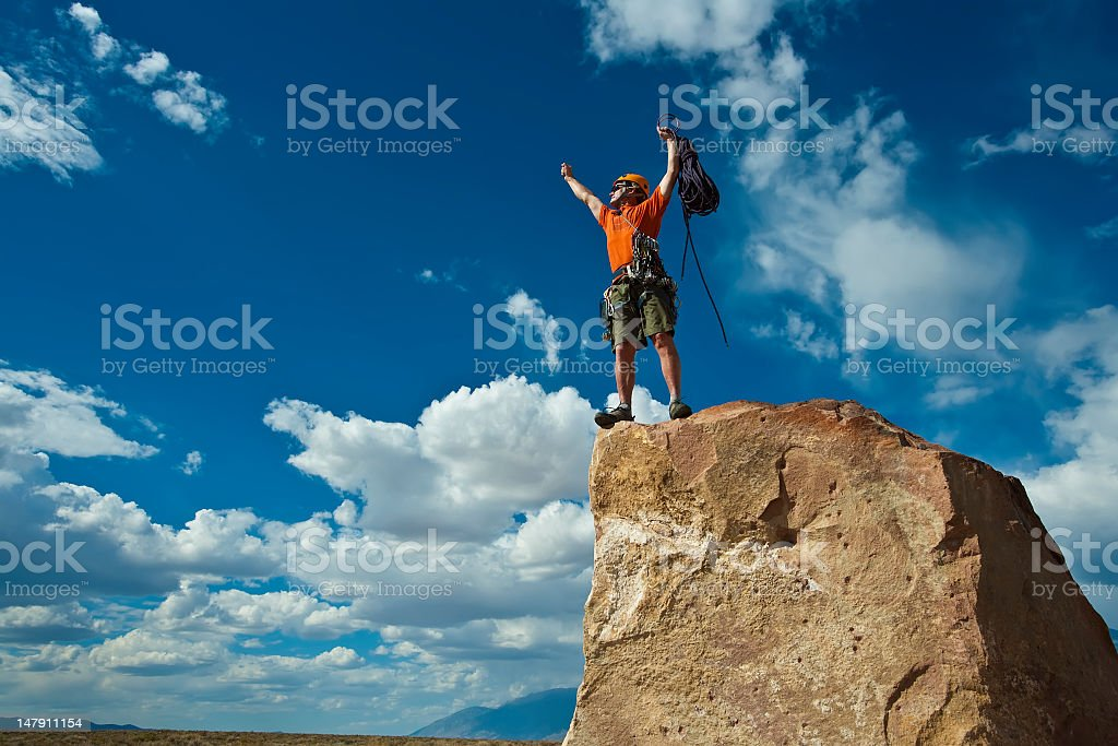 Rock climber cheering his summit royalty-free stock photo
