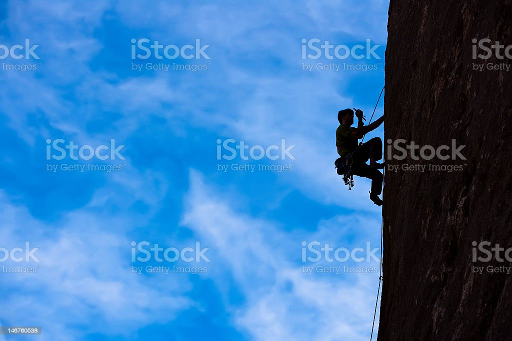 Rock climber climbing a cliff about to fall off stock photo