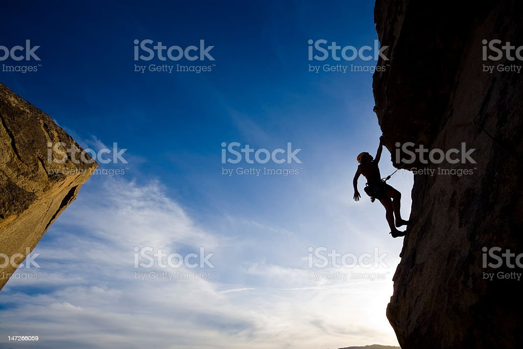 Rock climber clinging to a cliff as he climbs higher royalty-free stock photo