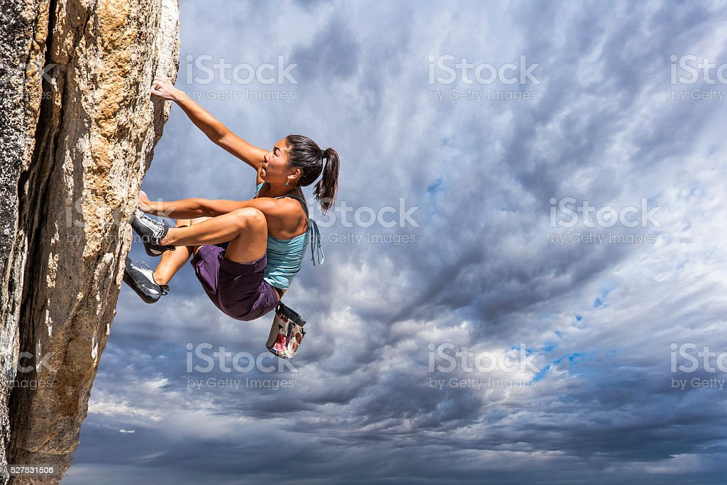 Rock climber clinging to a cliff. stock photo