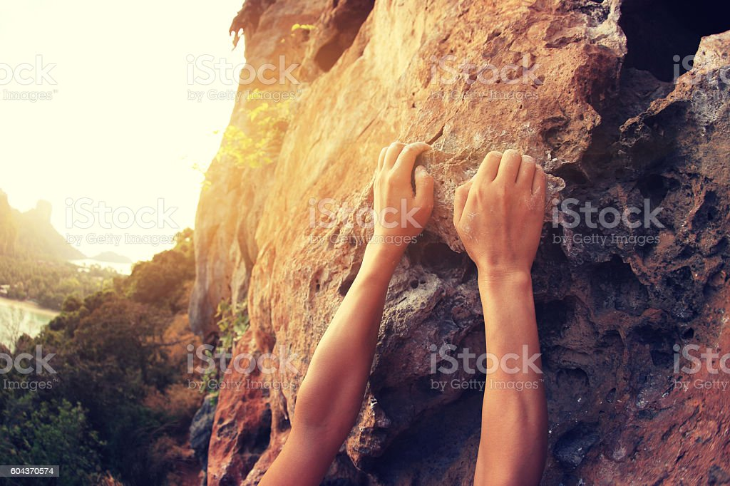 rock climber hands climbing at seaside mountain cliff rock stock photo