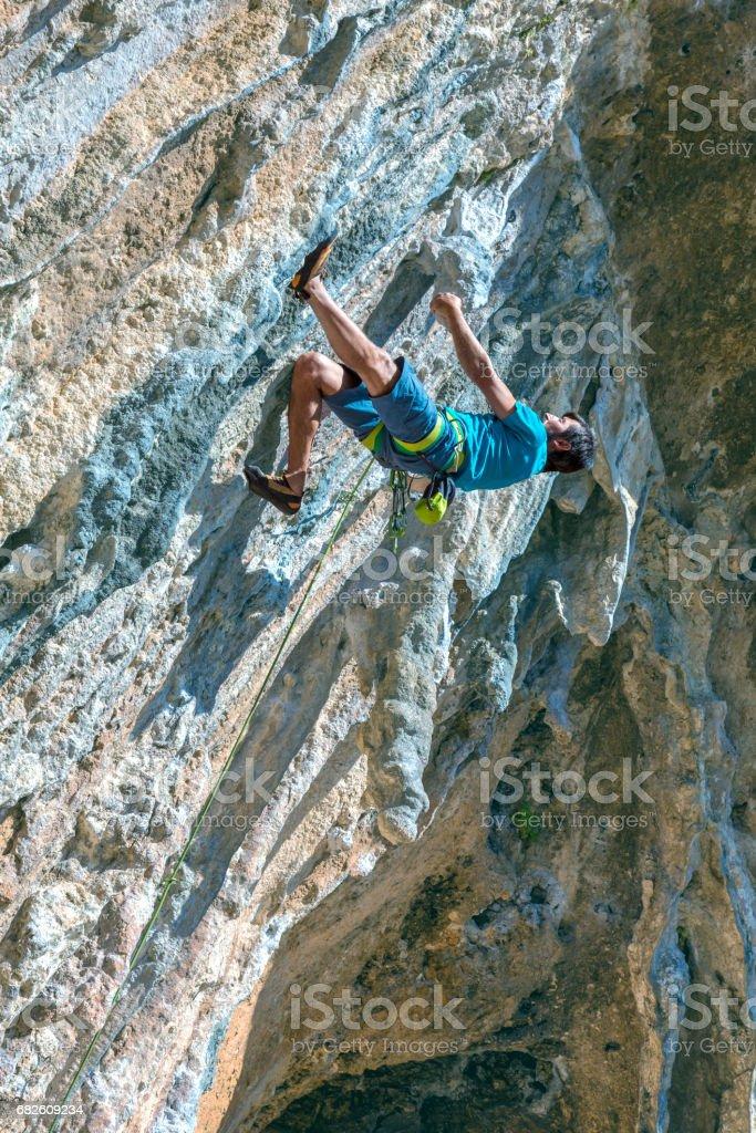 Rock Climber hanging high on natural Rock looking up stock photo