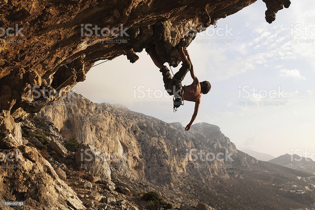 A rock climber hanging on a cliff on a sunny day stock photo