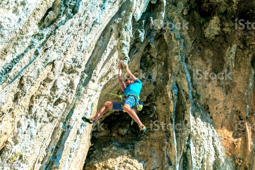 Rock Climber hanging on unusual rocky formation stock photo