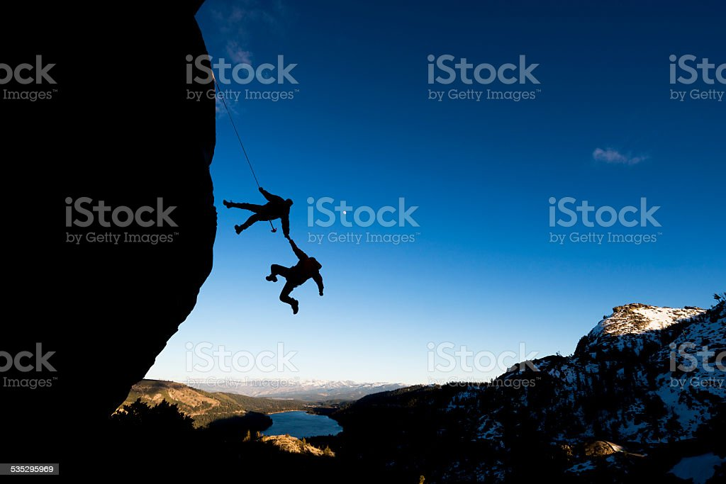 rock climber helping another stock photo