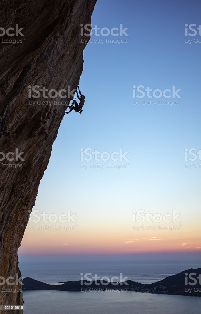 Rock climber on overhanging cliff at sunset stock photo