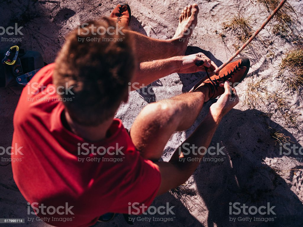 Rock climber putting on climbing shoes before ascent stock photo