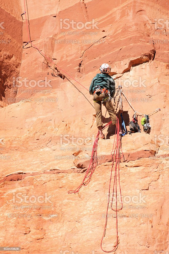 Rock Climber Retrieves Belaying Ropes stock photo
