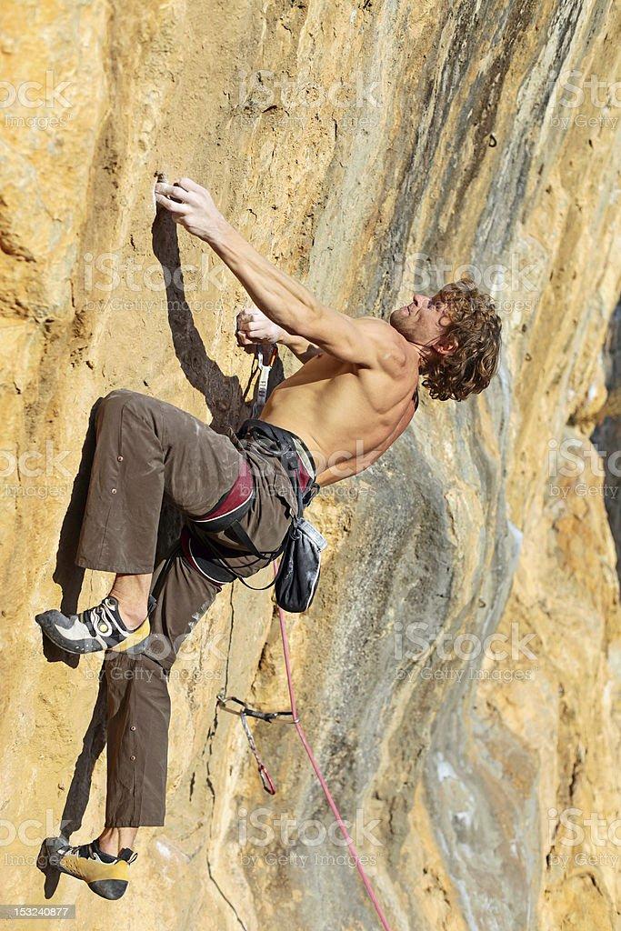 Rock climber struggling to take next handhold royalty-free stock photo