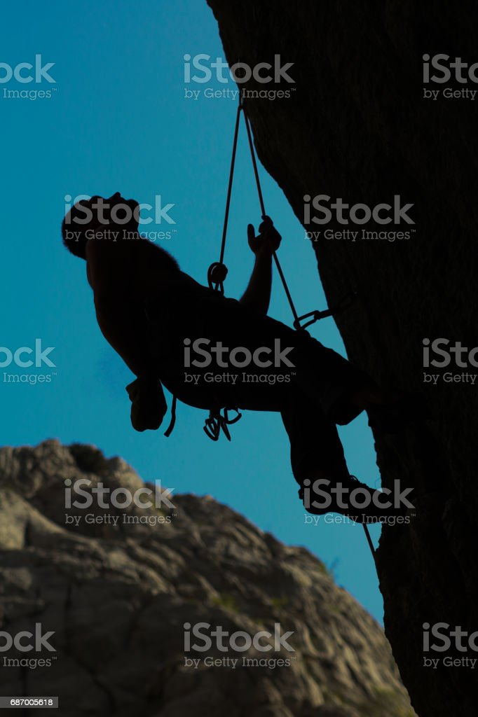 Rock climber with climbing equipment and looking up. stock photo