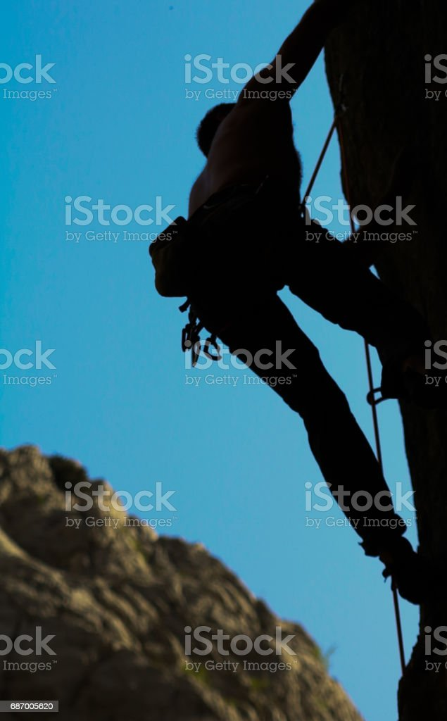 Rock climber with climbing equipment in divide. stock photo