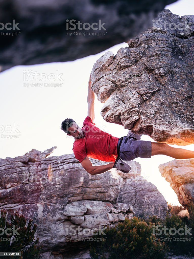 Rock climber with hand in chalk bag hanging on boulder stock photo
