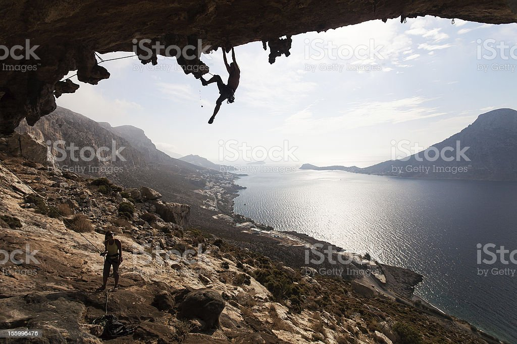 Rock climbers against picturesque sea view before sunset royalty-free stock photo