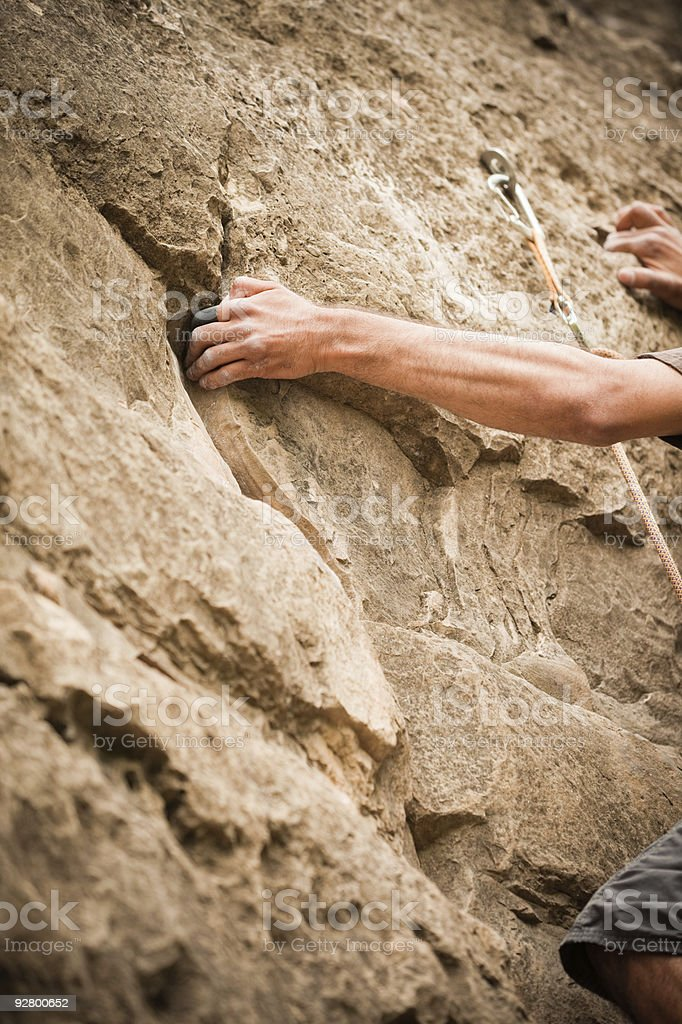 Rock Climber's arm holding onto a crack royalty-free stock photo