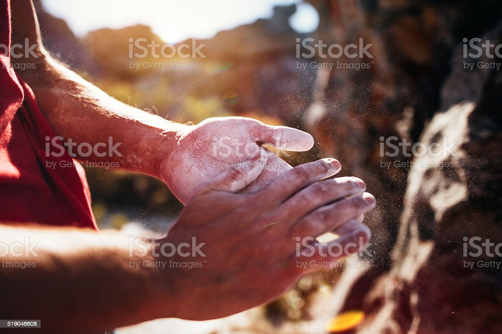 Rock climber's hands rubbing chalk in preparation for climbing ascent stock photo