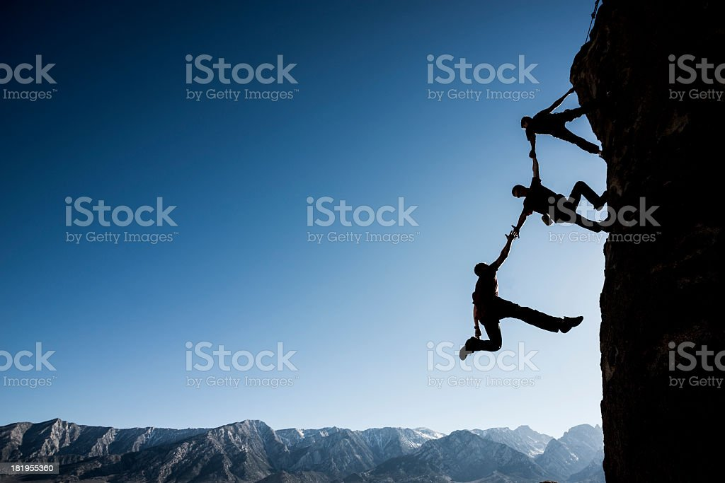 Rock climbers helping man in danger of falling stock photo