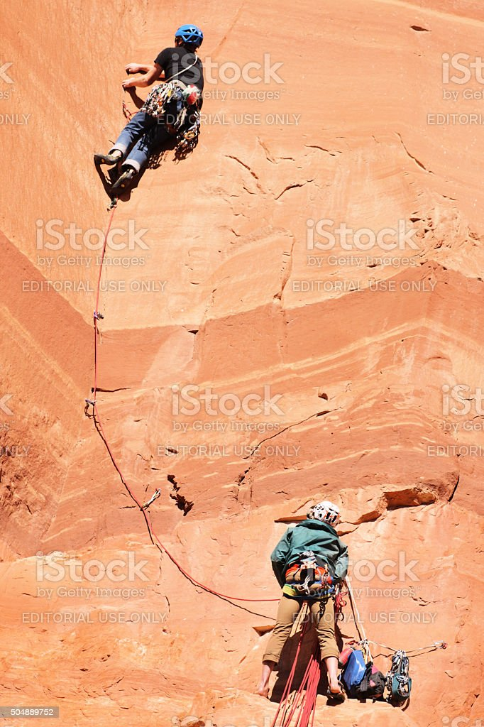 Rock Climbers Rappelling Belaying Cliff stock photo