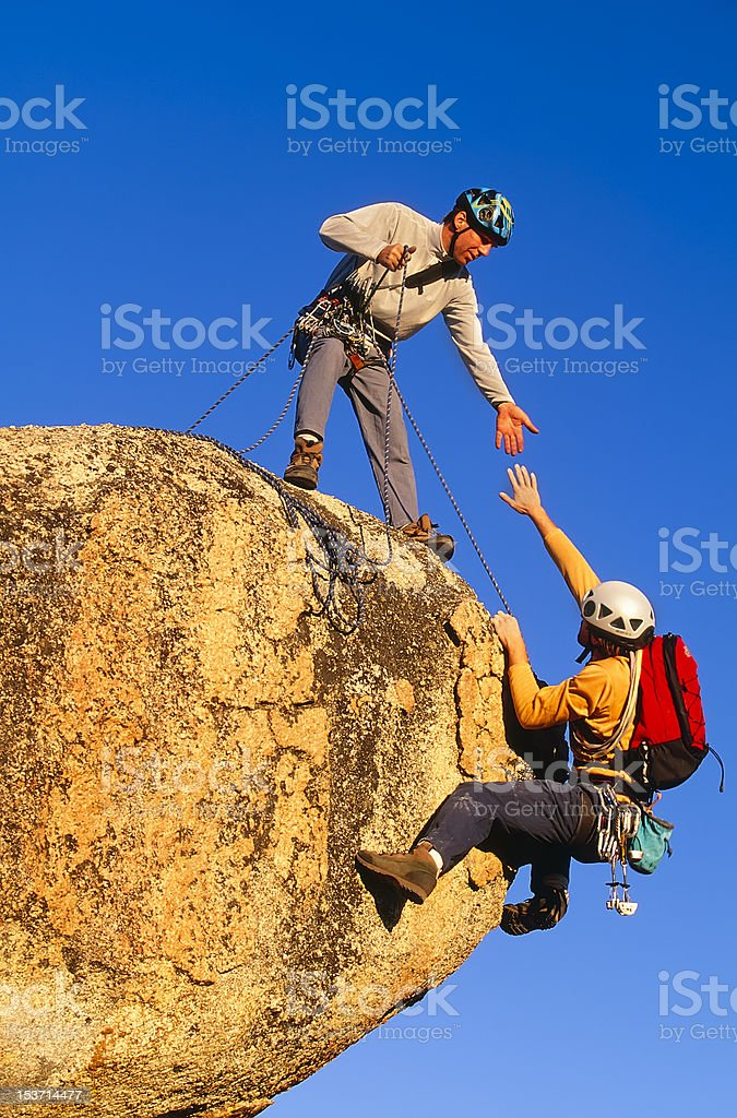 Rock climbing team reaching the summit. stock photo