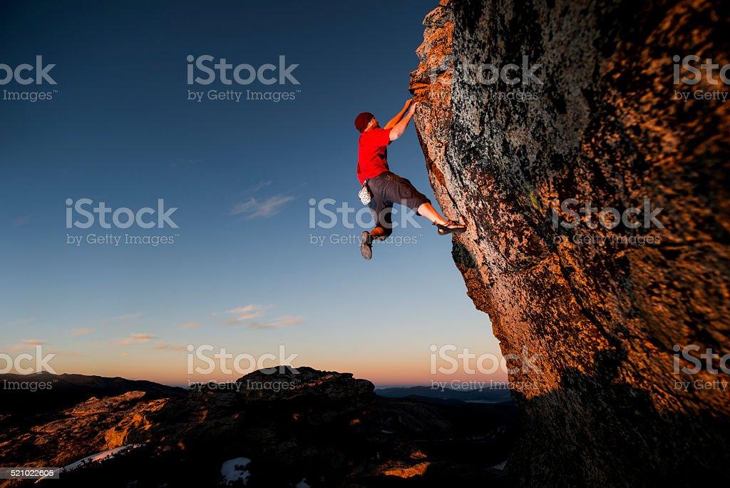 Rock climbing up a steep cliff stock photo