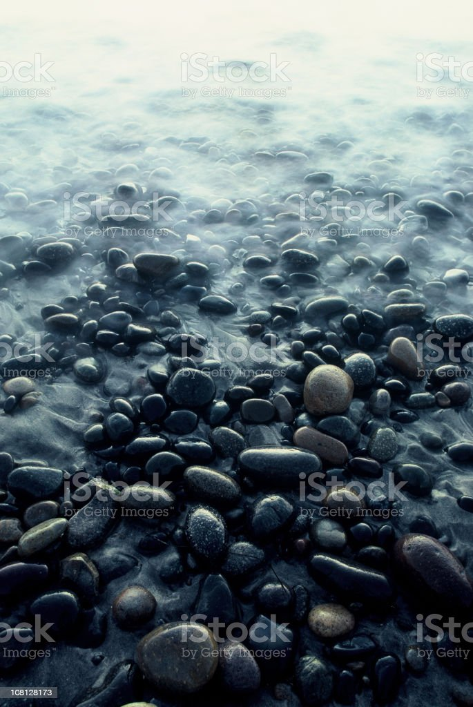 Rock Covered Beach with Calm Water stock photo