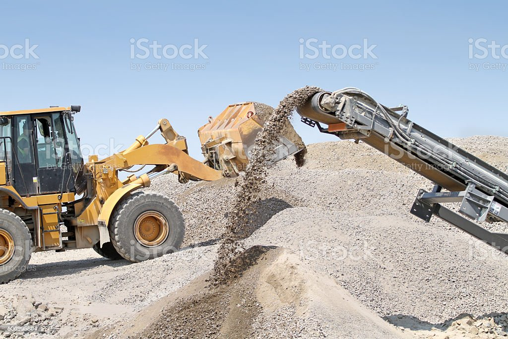 Rock Crusher And Front End Loader At Work stock photo