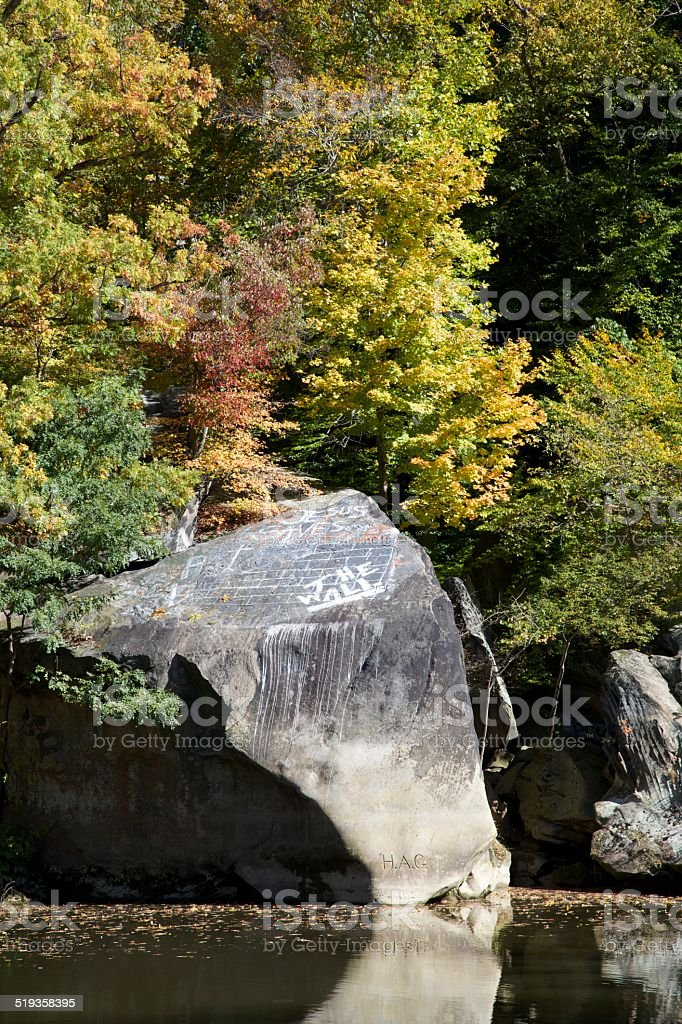 Rock in Cascade park on the black river with Graffiti stock photo