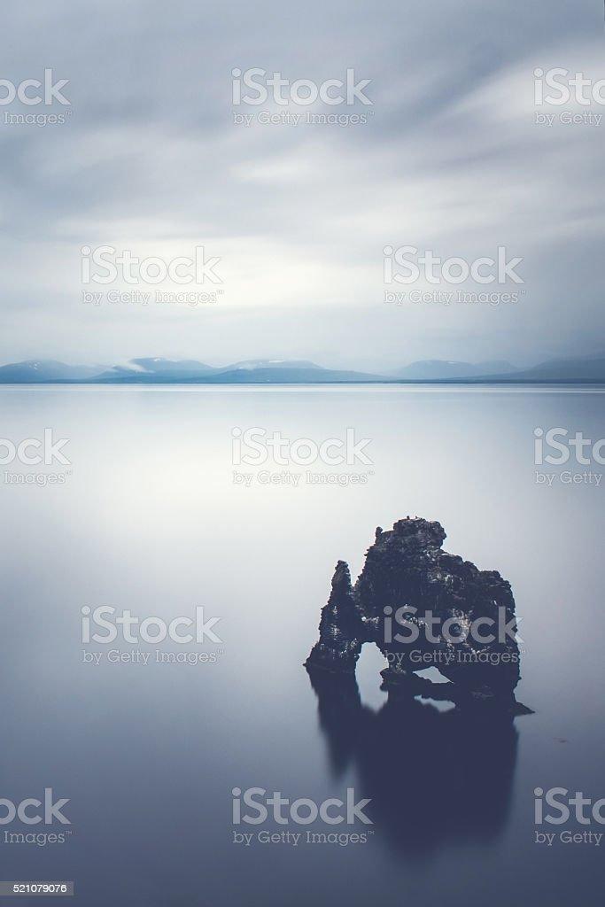 Rock in the calm sea stock photo