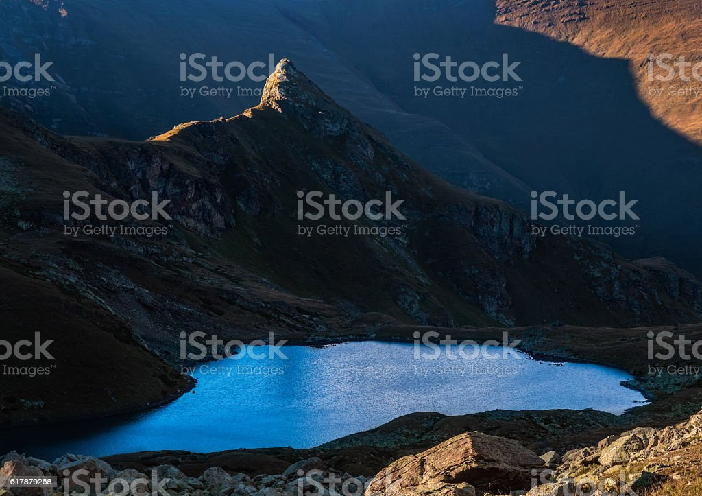 Rock in the light of sunset and mountain lake. stock photo