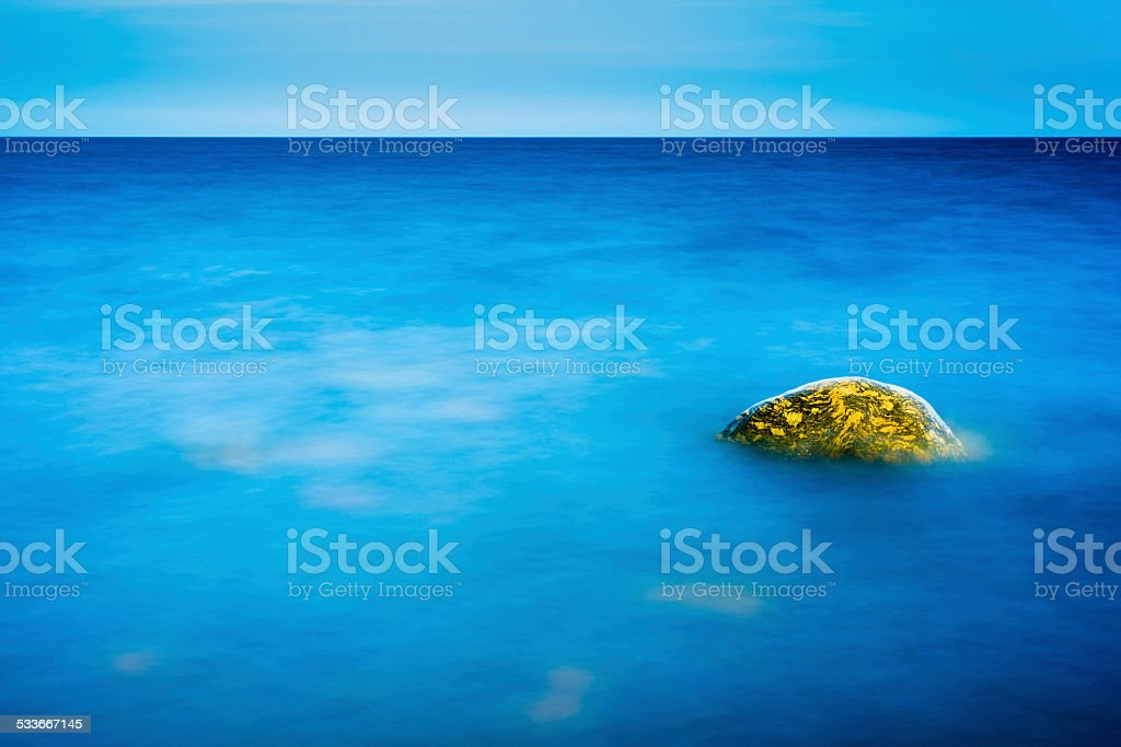 Rock in the still water stock photo