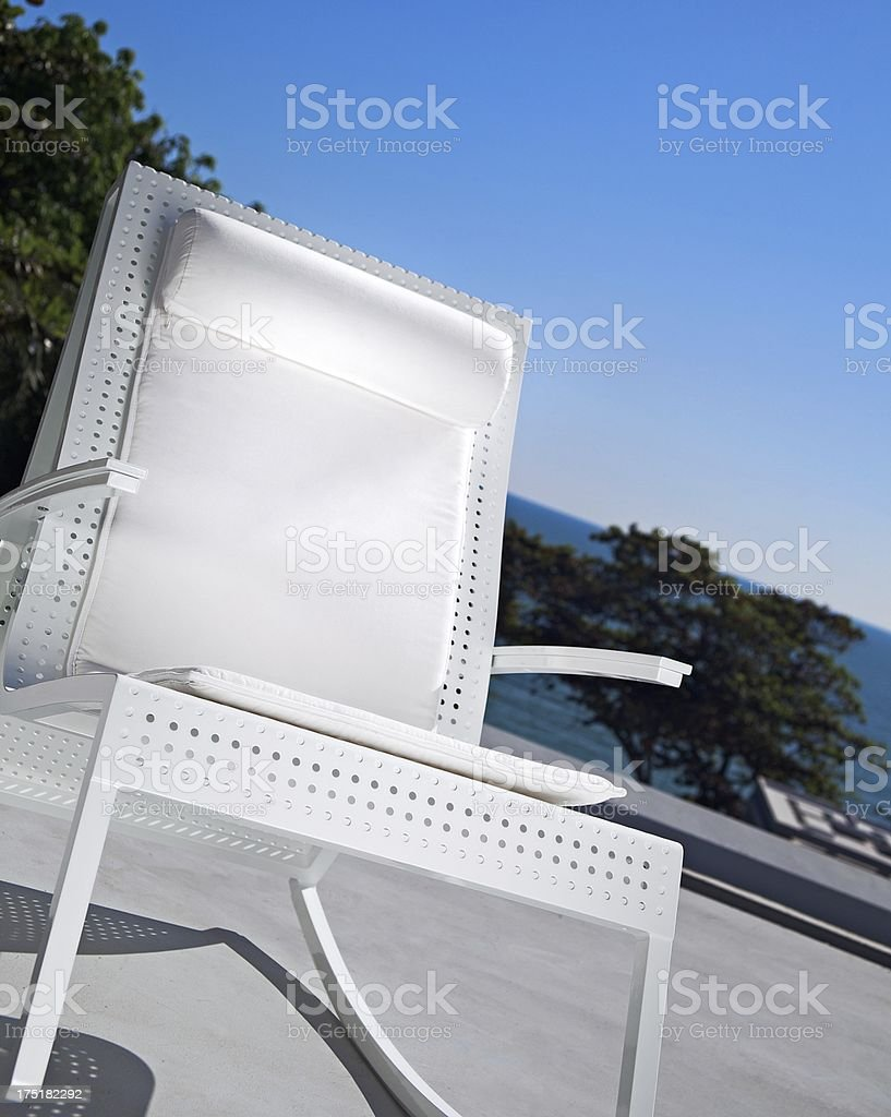 Rock in White Roching Chair to the Sea's Waves royalty-free stock photo