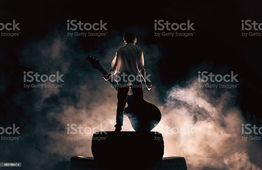 Rock musician and large guitar, a lot of smoke stock photo
