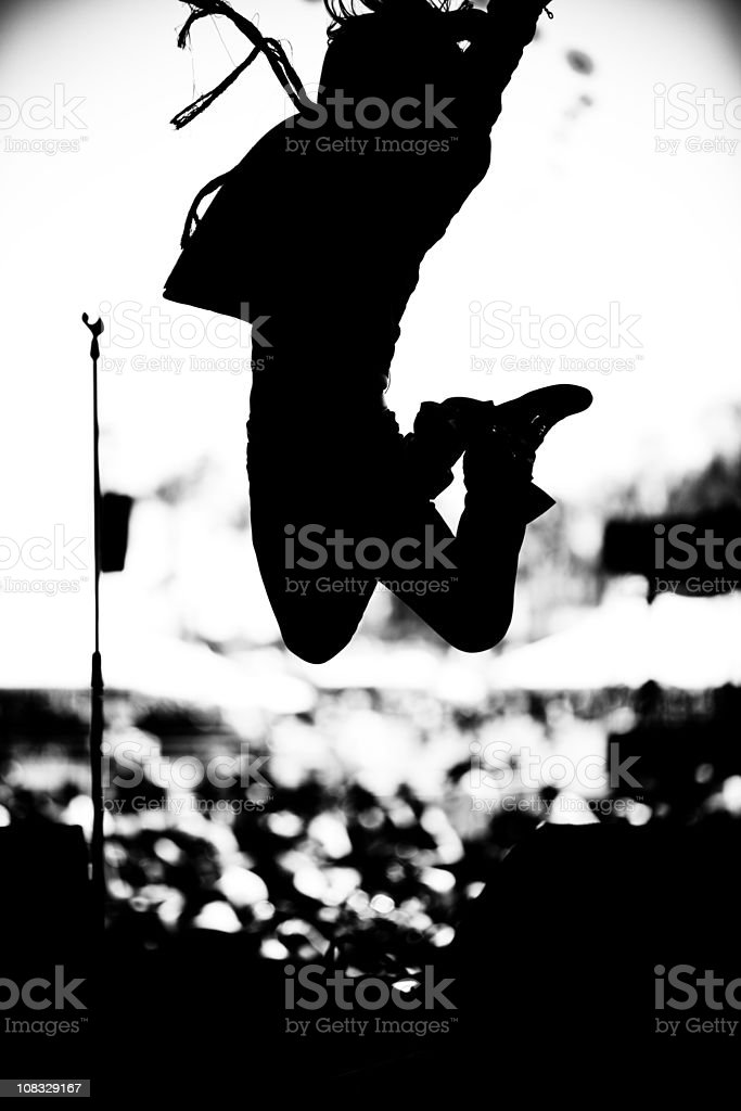 Rock musician leaping through the air stock photo