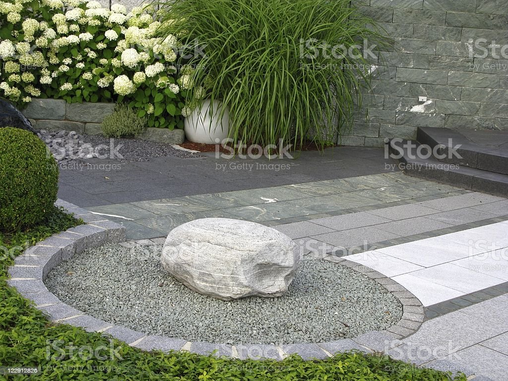 Rock on a circular platform of grass stock photo