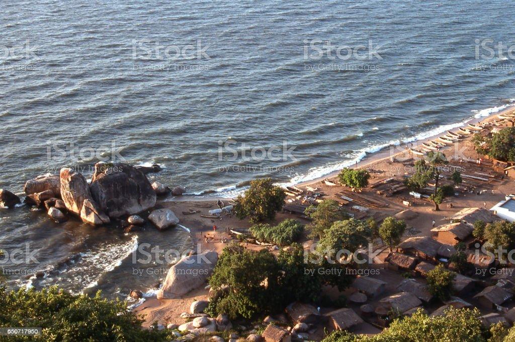 Rock outcrops by shoreline village along Lake Malawi Malawi Africa stock photo