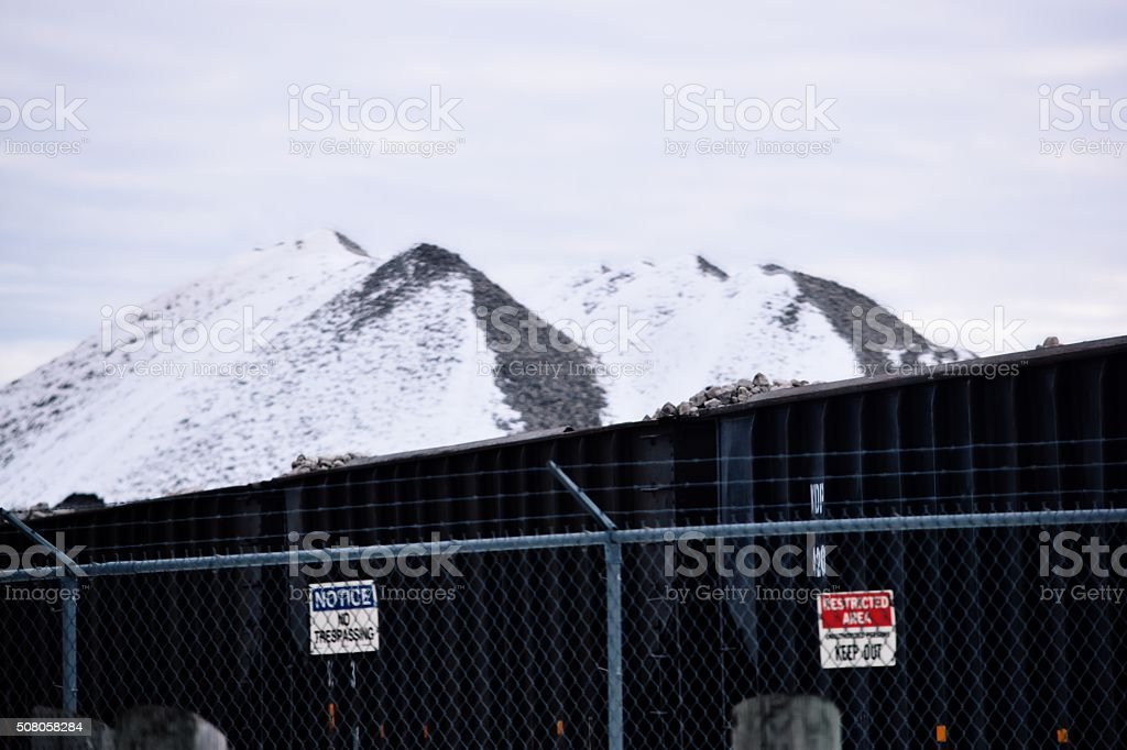 rock piles and traincars with barb wire fence royalty-free stock photo
