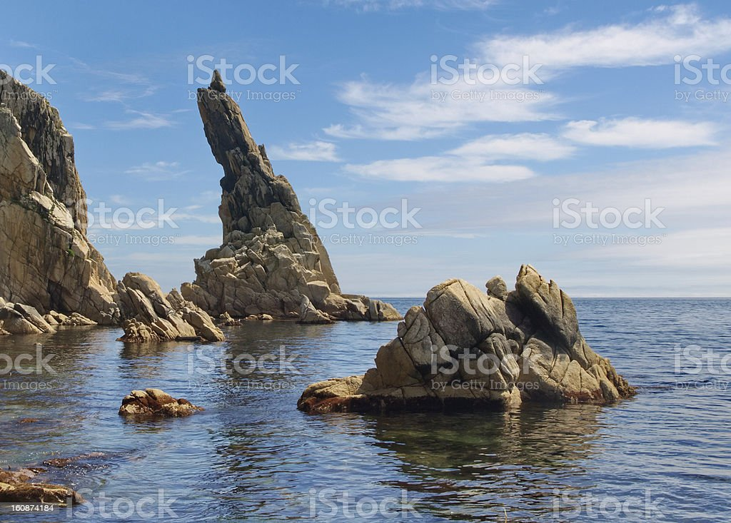 Rock sticking vertically out of the water royalty-free stock photo