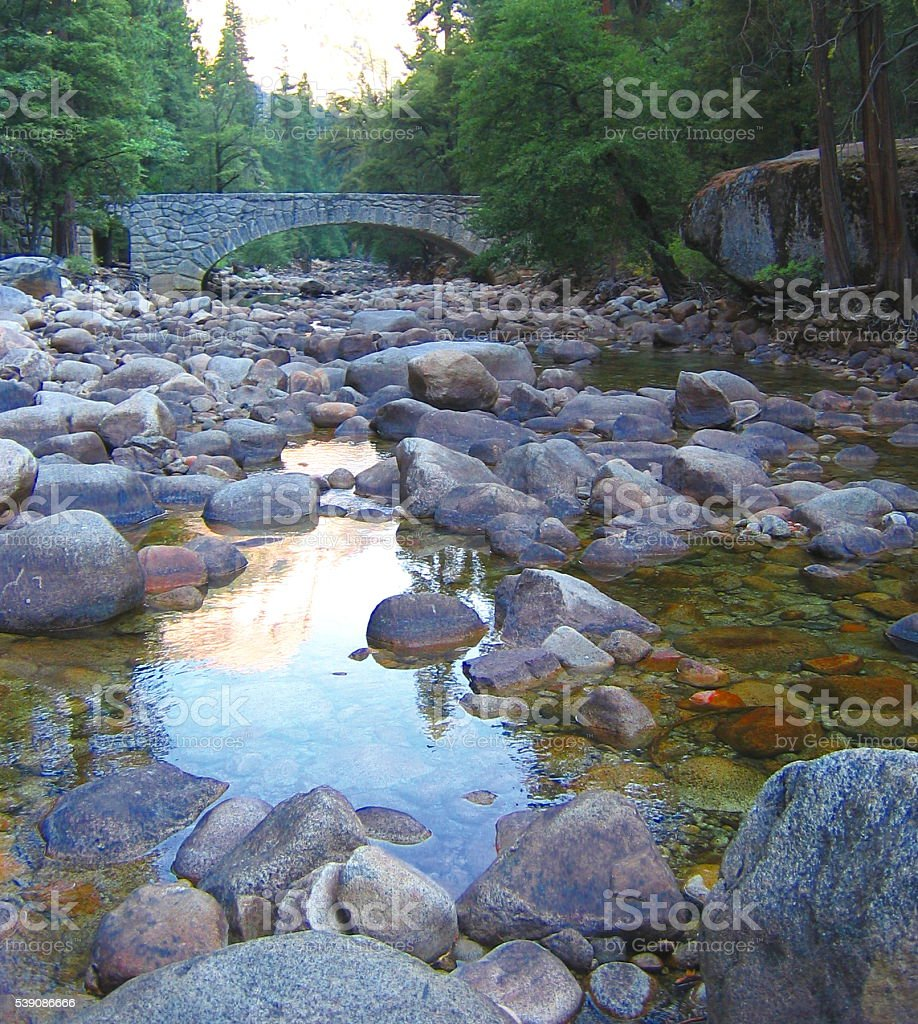 Rock Strewn Mountain Stream with Stone Bridge stock photo