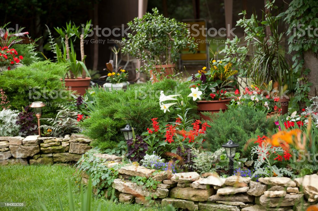 Rock walled flower filled landscape on edge of green lawn royalty-free stock photo