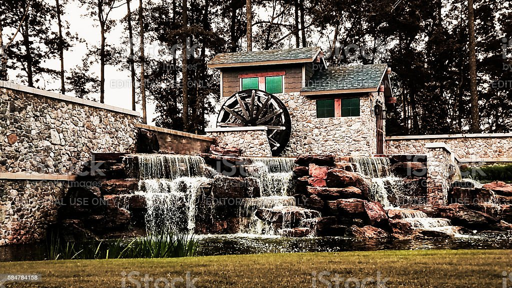 Rock water fountain feature with rustic wheel. stock photo