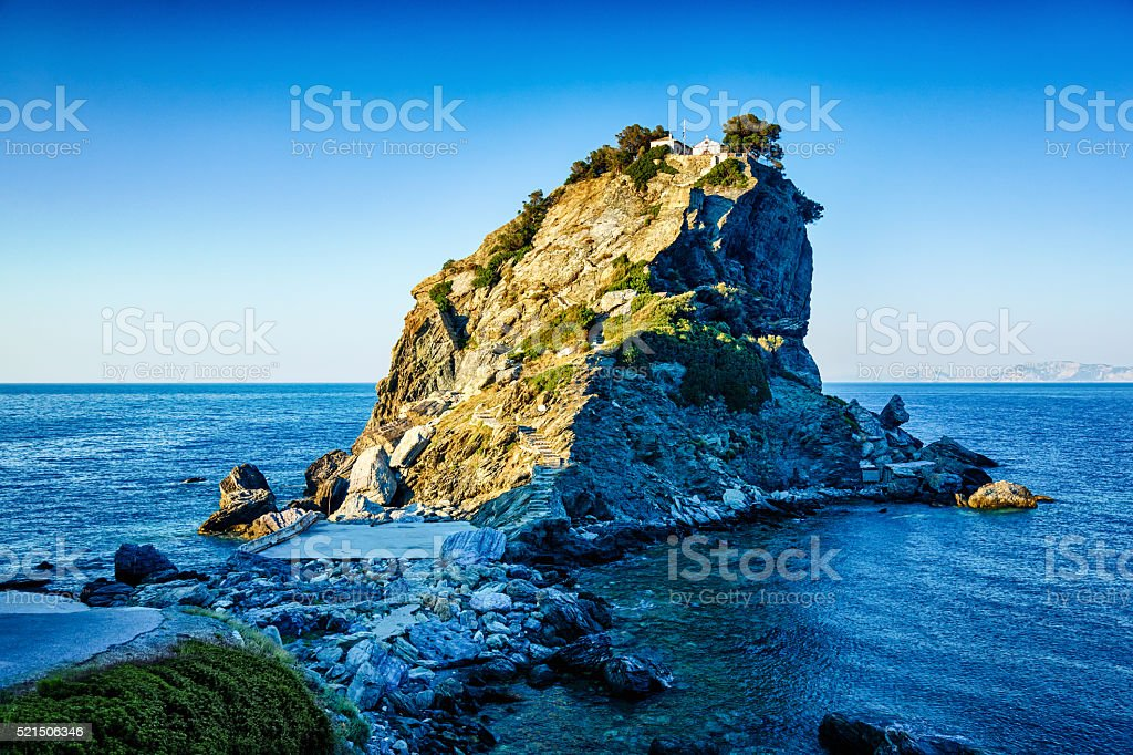 Rock with Agios Ioannis church on Skopelos island at sunset stock photo