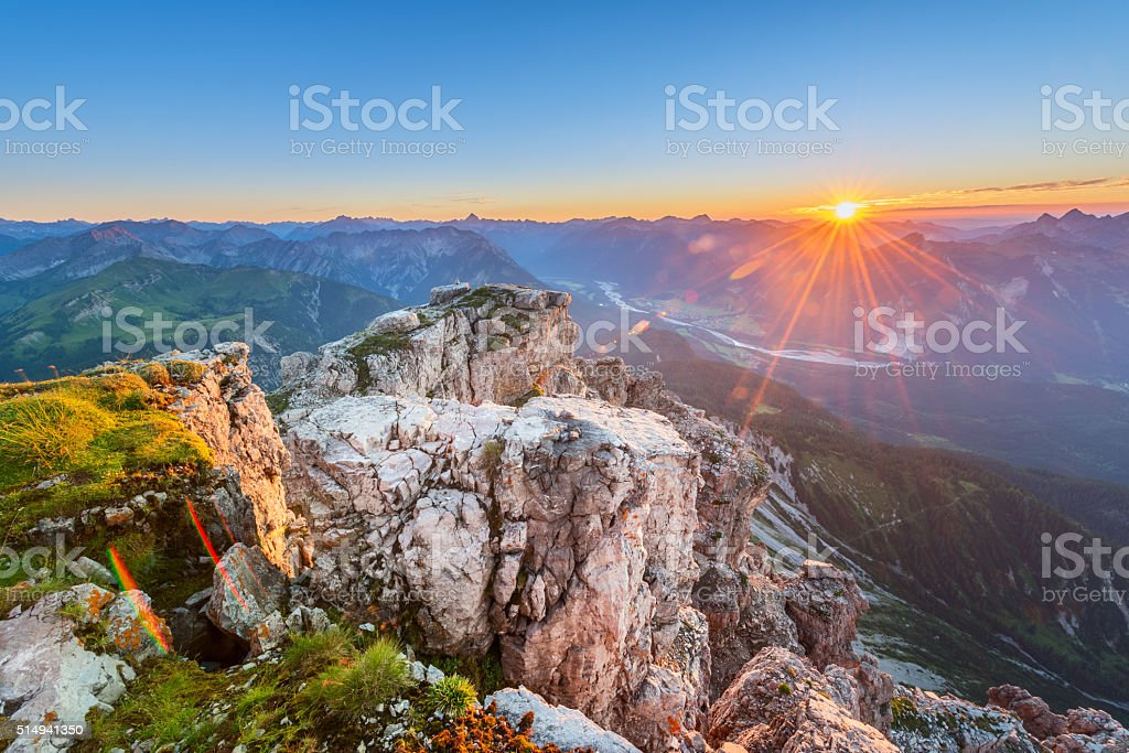 rock with grass on top of tirol mountains at sunset stock photo