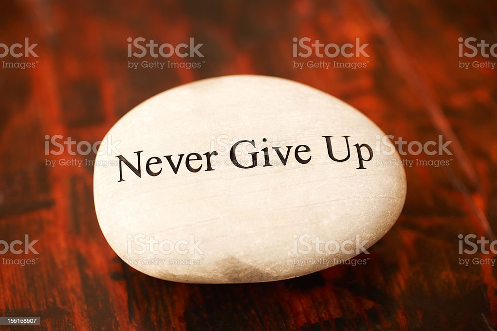 Rock with 'Never Give Up' written on it royalty-free stock photo
