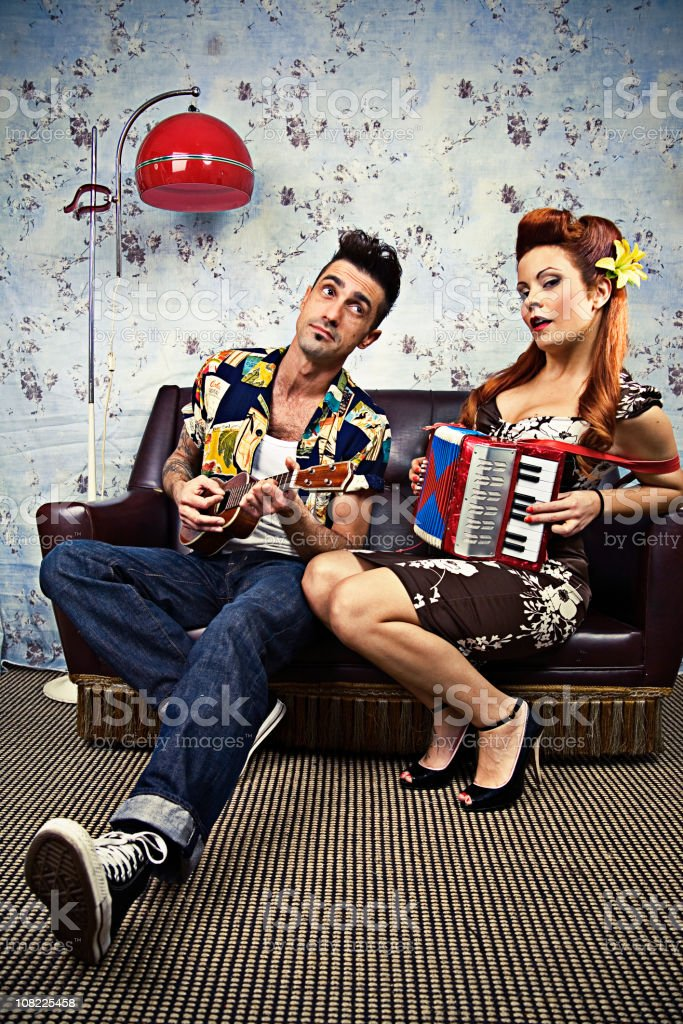 Rockabilly Couple Playing Ukelele and Accordion on Couch royalty-free stock photo