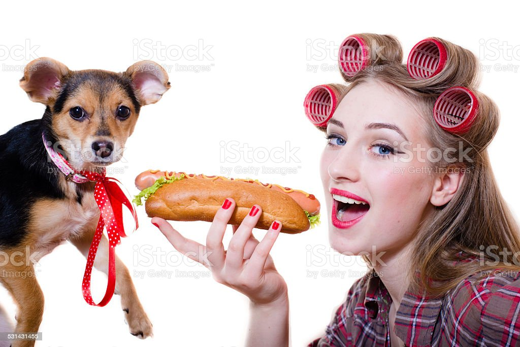 Rockabilly girl sharing hotdog with puppy stock photo