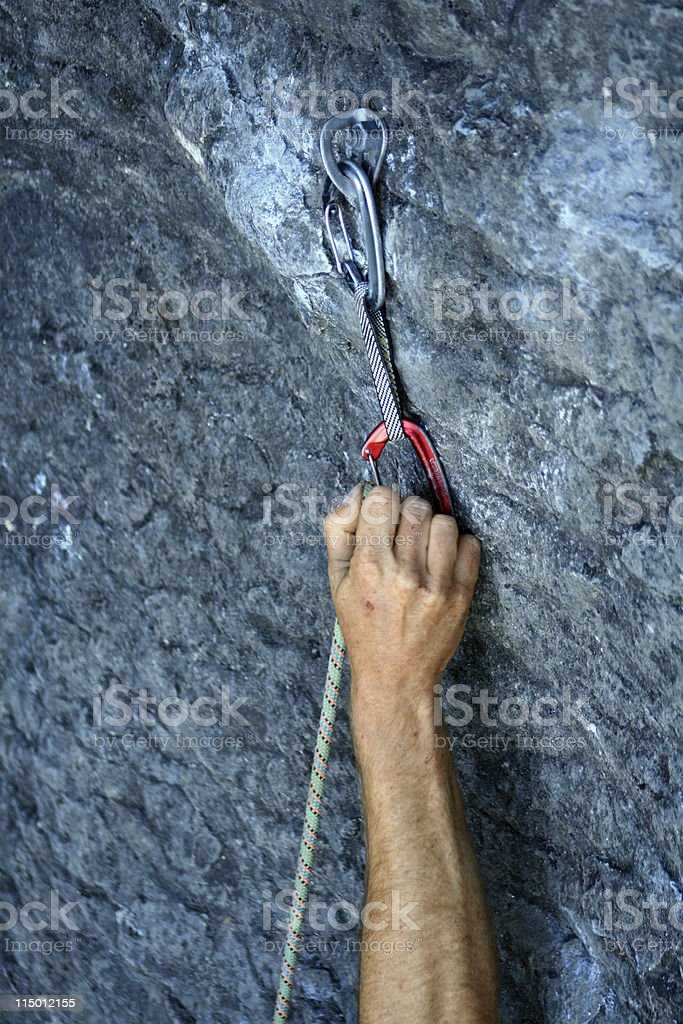 Rockclimber clipping a rope stock photo