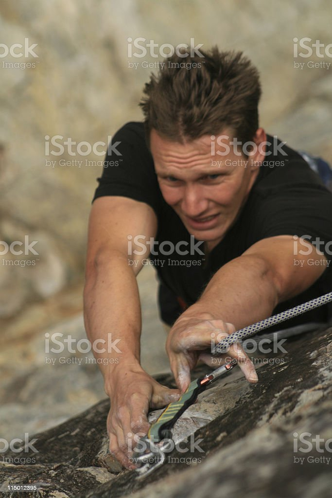 Rockclimber clipping a rope royalty-free stock photo