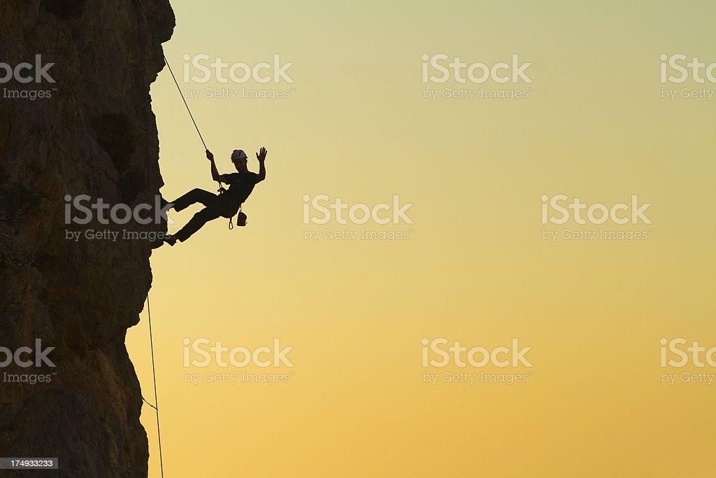 Rockclimber waving stock photo